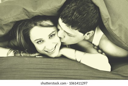 happy young couple in bed at morning