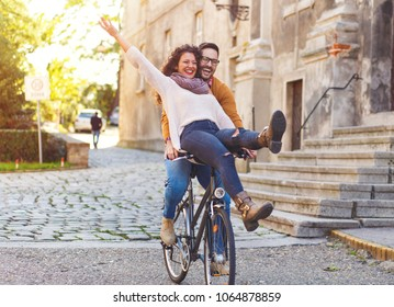 Happy young couple with a bicycle on sunny day in the city.