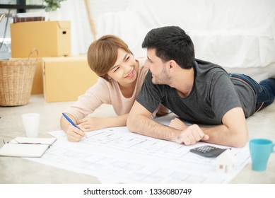 Happy young couple with blueprints planning their new house. Smiling each other.