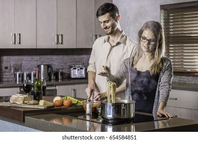 happy young couple bonding dinner cooking in the kitchen