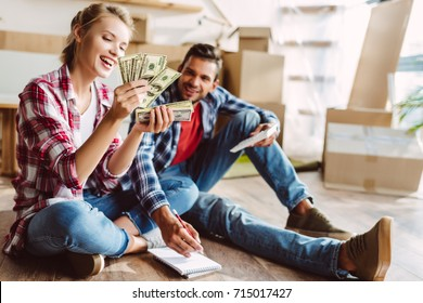 happy young couple with calculator and dollar banknotes counting money in new apartment