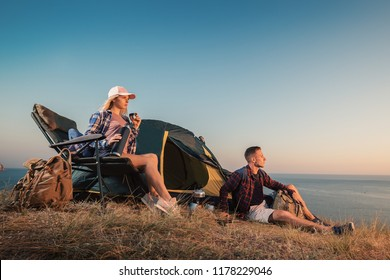 Happy young couple at campsite tent near seaside. Man and woman camp on summer outdoor adventure hiking trip in mountain.