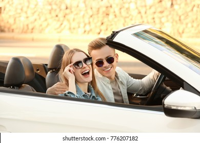 Happy young couple in car on road trip