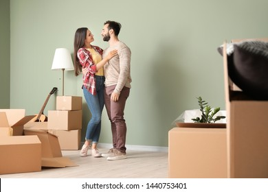Happy young couple with cardboard boxes in their new house