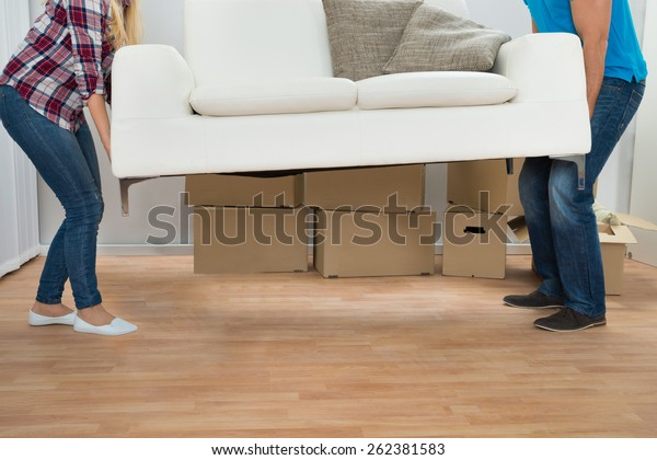 Happy Young Couple Carrying Couch In New Home