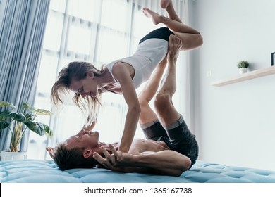 Happy young couple carrying and lift girl by his feet upside down