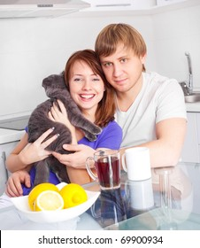 happy young couple with a cat drinking tea with lemon in the kitchen at home
