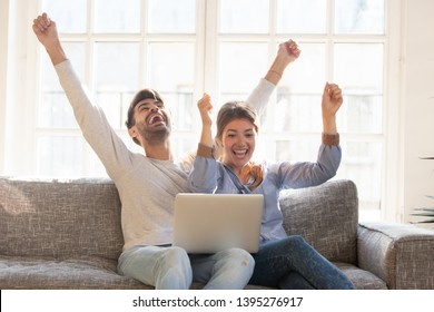 Happy young couple celebrate online victory, screaming with joy raising hands, looking at laptop screen together, wife and husband receive good news, achievement, new great offer opportunity, success