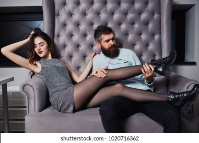 Happy young couple celebrate valentines day sitting on the couch. Fashion couple sitting on couch together, looking away from the camera. Enjoying time together. Beautiful couple bonding to each other