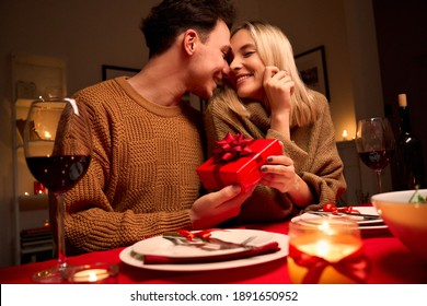 Happy young couple celebrating anniversary or Valentines day having romantic dinner at home table. Loving man giving red gift box hugging beloved woman making present surprise on date in candle light. - Shutterstock ID 1891650952