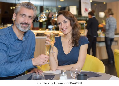 happy young couple celebrating birthday wih champagne at the restaurant