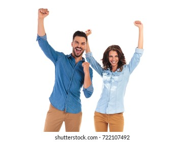happy young couple celebrating success with hands up in the air on white background