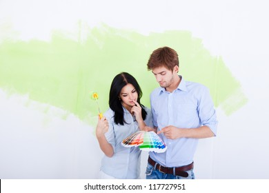 happy young couple choose palette color pantone paint in green color white wall of their new apartment home