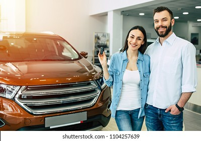 Happy young couple chooses and buying a new car for the family in the dealership.