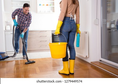 Happy young couple cleaning home together. Man hoovering and girl holding bucket for mopping floor
