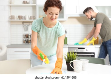 Happy young couple cleaning kitchen together
