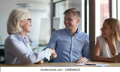 Happy young couple clients handshake old manager broker make insurance investment bank deal, family customers sign mortgage loan contract shake hand of realtor insurer buy services meeting saleswoman
