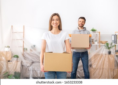 Happy young couple collecting clothes into boxes and planning repair, moving to new place, copy space
