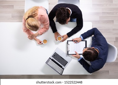 Happy Young Couple Consulting Male Friendly Financial Advisor With Coffee Cups At Office Desk