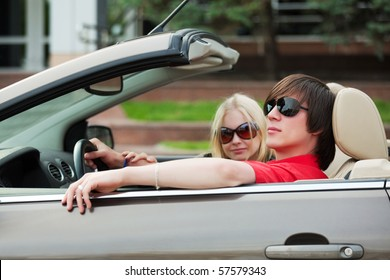 Happy young couple in the convertible.