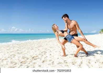Happy young couple dancing with love at the beach