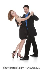 Happy young couple dancing on white background