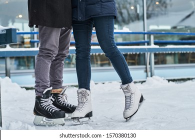 Happy young couple dating in the ice rink, hugging and enjoying winter time
