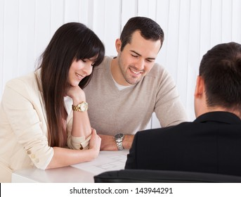 Happy Young Couple Discussing With Consultant In Office