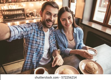 Happy young couple is doing selfie, looking at camera and smiling while sitting at the cafe