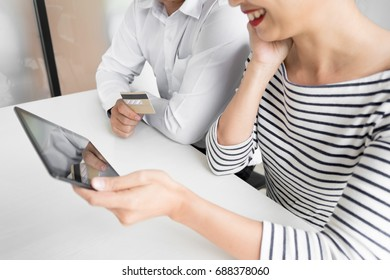 Happy young couple doing  shopping online at home with tablet