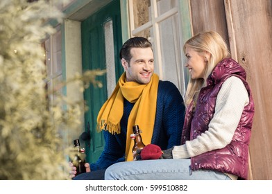 Happy young couple drinking beer and looking at each other while sitting on porch