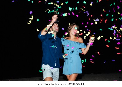 Happy young couple drinking champagne and celebrating at night