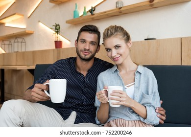 happy young couple drinking coffee and smiling at camera in cafe