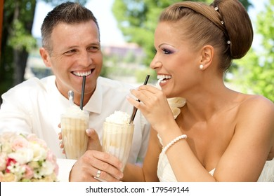 Happy young couple drinking ice coffee through straw on wedding-day outdoors. Laughing happy.
