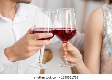 Happy young couple drinking wine on romantic date in cafe, closeup