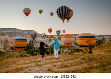 happy young couple during sunrise watching the hot air balloons of Kapadokya Cappadocia Turkey