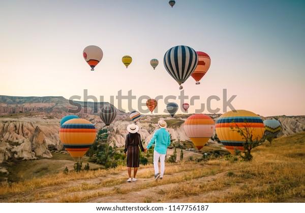 glückliches junges Ehepaar bei Sonnenaufgang mit Blick auf die Heißluftballons von Kapadokya Kappadocia Türkei