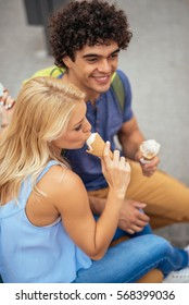 Happy young couple eating ice cream outdoors and enjoying the time they spend together.