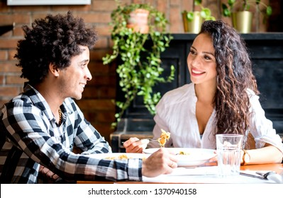 Happy young couple eating lunch together at restaurant, african american people having fun