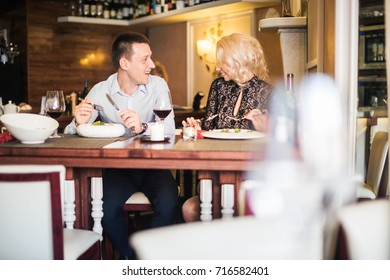 Happy young couple eating pastries in a pastry shop.