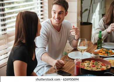 Happy young couple eating and talking at the table at home