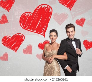 happy young couple in elegant tuxedo and dress laughing together while holding arms on hearts background