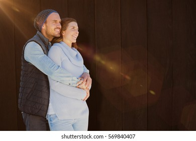 Happy young couple embracing against wood background