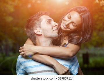 Happy young couple embracing in the park