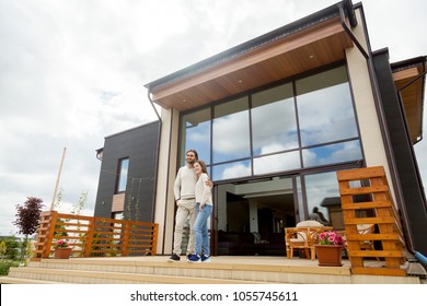 Happy young couple embracing standing outside big house on front porch, smiling owners enjoying luxury real estate wood and glass exterior design, buying home, mortgage loan, vacation rentals concept