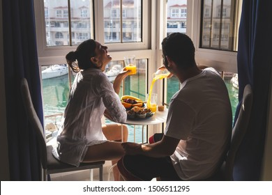 Happy young Couple Enjoying Breakfast  on the terrace at the marina. Relationship and lifestyle concept.