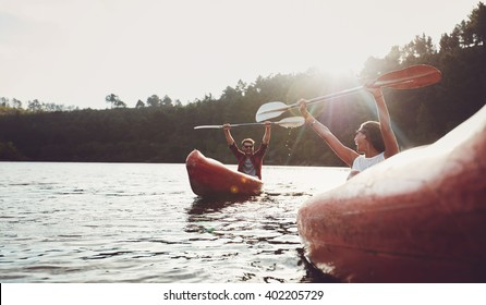 Happy young couple enjoying canoeing on summer day. Young man and woman having fun during kayaking.