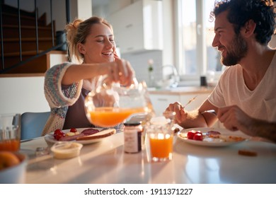 A happy young couple enjoying fresh orange juice for a breakfast on a beautiful sunny morning at home. Relationship, love, together, breakfast