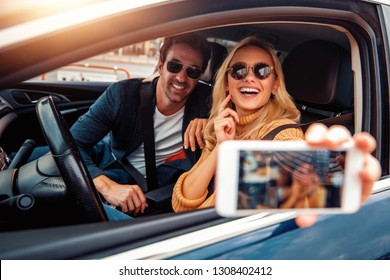 Happy young couple enjoying on a long drive in a car,takong selfie.