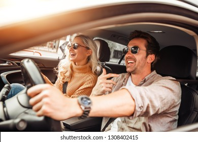 Happy young couple enjoying on a long drive in a car.